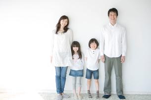 壁際に並ぶ親子4人の写真素材 [FYI03212494]
