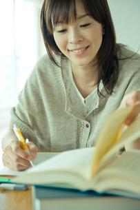 本のページをめくり勉強する20代女性の写真素材 [FYI03212542]
