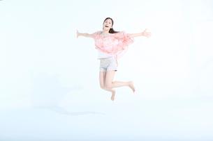 両手を広げる笑顔の20代女性の写真素材 [FYI03212800]