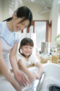 台所で食器を洗っている親子の写真素材 [FYI03212970]