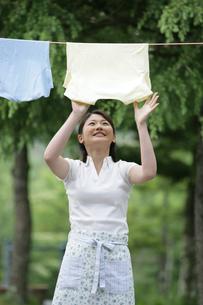 屋外で洗濯物を干す女性の写真素材 [FYI03213006]