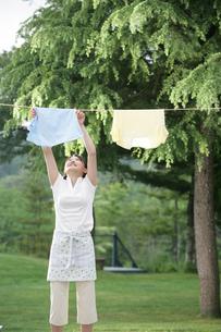 屋外で洗濯物を干す女性の写真素材 [FYI03213007]