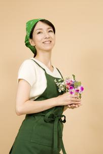 花束を持ったエプロン姿の女性の写真素材 [FYI03213113]
