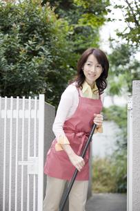 玄関先をほうきで掃く女性の写真素材 [FYI03213119]