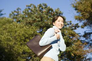鞄をかけて歩く女性の写真素材 [FYI03213132]