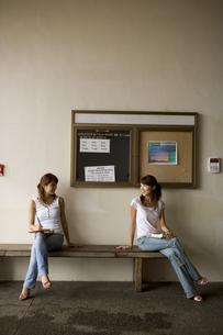 ベンチに座って顔を見合わせる2人の写真素材 [FYI03213176]