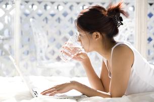水を飲みながらパソコンを見る女性の写真素材 [FYI03213180]