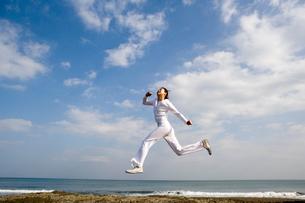 海辺でジャンプしている女性の写真素材 [FYI03213204]