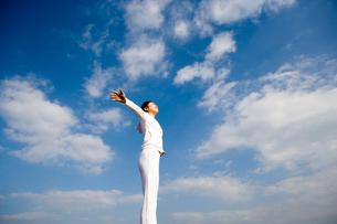 両手を広げて立つ女性の後姿の写真素材 [FYI03213210]