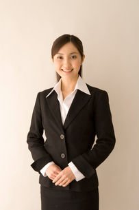 両手を前で合わせるスーツの女性の写真素材 [FYI03213212]