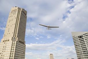 ビルの合間を飛ぶ飛行機の写真素材 [FYI03213244]