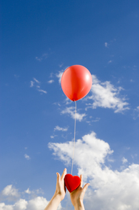 風船からぶら下がるハートを持つ手の写真素材 [FYI03213278]