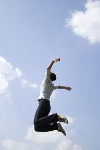 青空へジャンプする女性の後姿の写真素材 [FYI03213325]