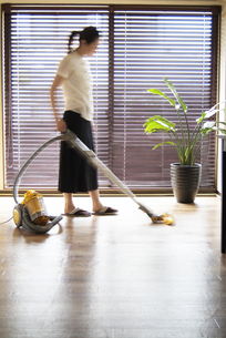 リビングで掃除機をかける女性の写真素材 [FYI03214014]