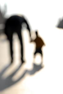 坂道を歩く親子のシルエットの写真素材 [FYI03214164]