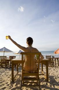 浜辺でビールを掲げる水着の女性の写真素材 [FYI03214257]