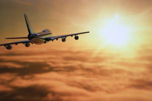夕日に向かって飛ぶ飛行機の模型の写真素材 [FYI03214319]