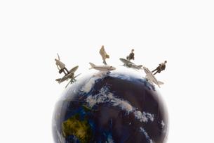 地球儀の上で飛行機に乗った人形の写真素材 [FYI03214354]
