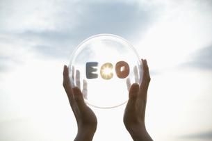 ECOと書かれた透明な球体をかざす手の写真素材 [FYI03214360]