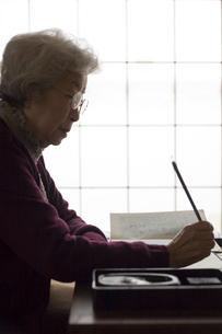 和室で書道をするシニア女性の写真素材 [FYI03214463]