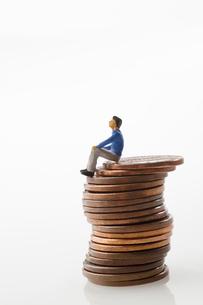 重なった1セントコインの上に座る男性の人形のイラスト素材 [FYI03214476]