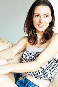 笑顔でリビングでくつろぐ20代女性のビューティーイメージの写真素材 [FYI03214965]