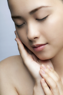 頬をなでる10代日本人女性のビューティーの写真素材 [FYI03214980]