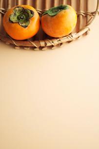 籐のトレイに乗った柿の写真素材 [FYI03215283]