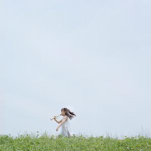 おもちゃのラッパを外で吹く女の子の写真素材 [FYI03215363]