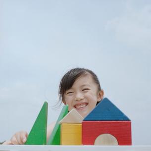 積み木で家を作る笑顔の女の子の写真素材 [FYI03215372]