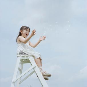 梯子に座りシャボン玉で遊ぶ女の子の写真素材 [FYI03215376]