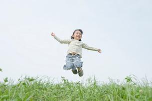 外でジャンプする女の子の写真素材 [FYI03215380]