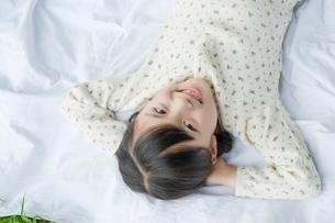 寝転がり空を見つめる笑顔の女の子の写真素材 [FYI03215386]