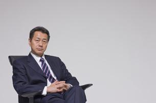 椅子に座るビジネスマンの写真素材 [FYI03215443]