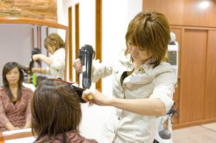 髪をブローする日本人美容師の写真素材 [FYI03215450]