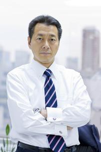 窓辺で腕組みするビジネスマンの写真素材 [FYI03215458]