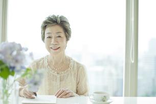 リビングで手紙を書く中高年女性の写真素材 [FYI03215479]