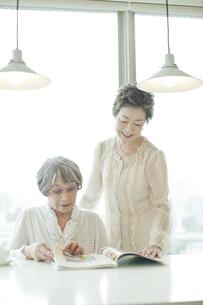 母親の横に立ち雑誌を読む中高年女性の写真素材 [FYI03215480]