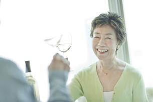 テーブルでワインを飲む笑顔の中高年夫婦の写真素材 [FYI03215486]