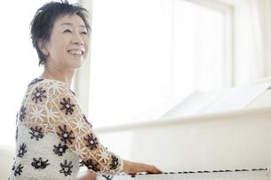 ピアノを弾き振り向く中高年女性の写真素材 [FYI03215489]