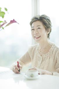 楽譜を書く笑顔の中高年女性の写真素材 [FYI03215493]