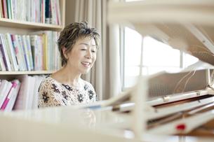 ピアノを弾き歌を歌う中高年女性の写真素材 [FYI03215494]