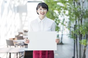 ホワイトボードを持つ女性店員の写真素材 [FYI03215570]