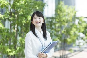 ファイルを持った笑顔のビジネスウーマンの写真素材 [FYI03215572]