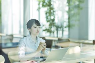 カフェでコーヒーを飲むビジネスウーマンの写真素材 [FYI03215601]