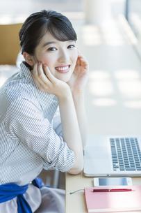 カフェで頬杖をついて笑顔のビジネスウーマンの写真素材 [FYI03215605]