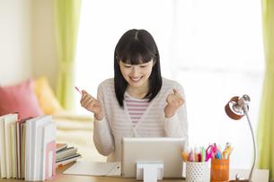 勉強机でタブレットPCを見てガッツポーズをする女の子の写真素材 [FYI03215613]