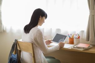 タブレットPCを見て勉強をする女の子の写真素材 [FYI03215648]