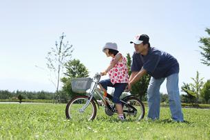 公園で自転車の練習をする親子の写真素材 [FYI03215688]