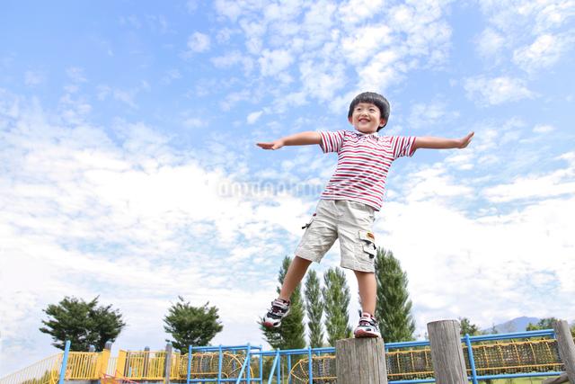 公園の遊具でバランスをとる少年の写真素材 [FYI03215697]
